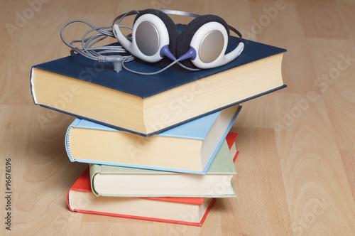 Poster Hörbücher gestapelt mit Kopfhörer auf hellem Holz