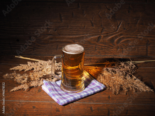 Fotobehang Thee Mug of light beer on wooden background