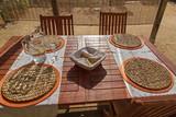 Mesa de madera preparada para cuatro comensales. Encima de la mesa una cesta con pan, jarra y copa con agua, manteles y reposa platos