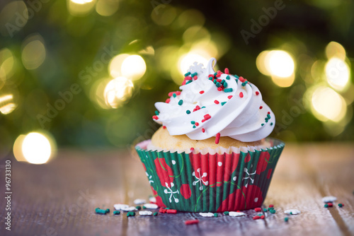 Poster Christmas cupcake with red and green sprinkles on rustic table