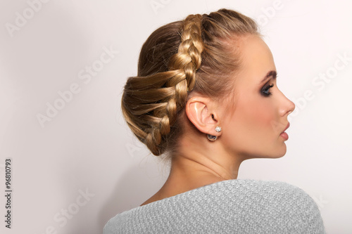 obraz lub plakat portrait of a beautiful young blonde woman on a light background with hairdo on her head. copy space.