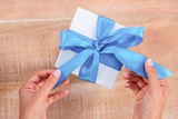 Woman presenting gift with blue ribbon