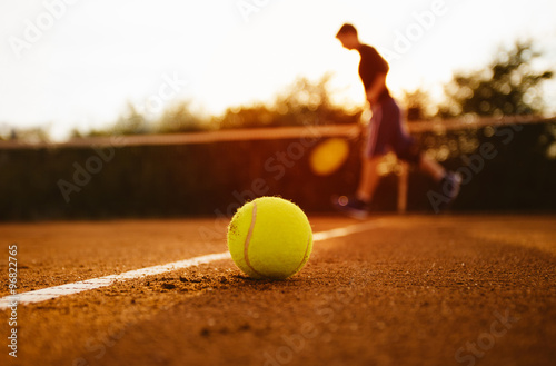 Tennis ball and silhouette of player Tablou Canvas