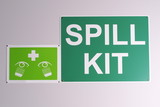 Emergency spill kit wall signs in green on off white background on a wall, Australia 2015