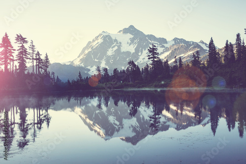 Jezioro otoczone lasem z górami w tle