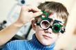 Постер, плакат: Optometrist doctor examines eyesight of child boy with phoropter