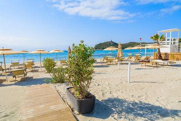 Sunchairs and umbrellas with white wooden lifeguard tower at Porto Giunco beach, Sardinia island, Italy