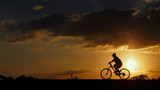 A woman rides a bicycle on the road when sunset: silhouette photo