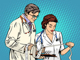 Fototapety Doctor and nurse looking cardiogram