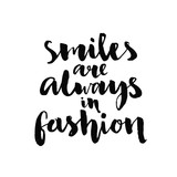 Smiles are always in fashion. Inspirational quote handwritten with black ink and brush, custom lettering for posters, t-shirts and cards. Vector calligraphy isolated on white background