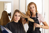 Beautiful blonde female hairdresser holding scissors, comb and h