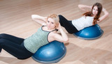 Women doing exercises for abdominal muscles on bosu ball in gym