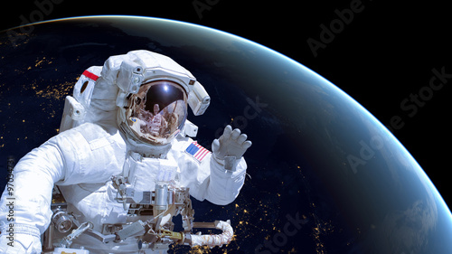 Close up of an astronaut in outer space, earth by night in the background. Elements of this image are furnished by NASA