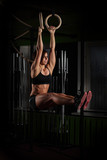 Fototapety Fit young woman on gymnast rings