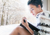 Fototapety Beautiful young brunette woman reading book wearing knitted poncho sitting home by the window. Snowy winter forrest background.