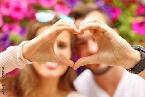 Young romantic couple showing a heart shape