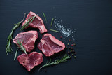 Top view of raw T-bone lamb steaks on a black wooden surface - 97119919