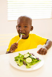 little boy eating salad