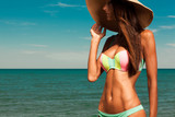 Fototapety Attractive girl enjoys hot summer day at the beach.