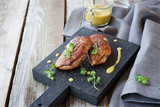 Fototapety Duck breast with orange sauce on a wooden board