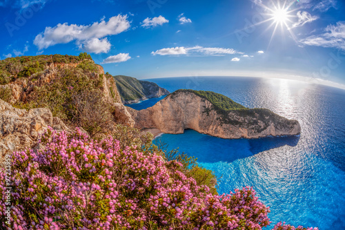 Zdjęcia na płótnie, fototapety na wymiar, obrazy na ścianę : Navagio beach with shipwreck and flowers against sunset, Zakynthos island, Greece