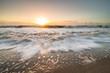 The rising tide rushing in towards land on Edisto Island, South Carolina during the sunrise.