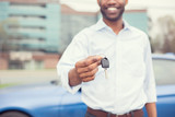 Happy smiling man holding car keys offering new blue car on background
