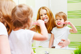 Fototapety mother and daughter child girl brushing her teeth toothbrushes f