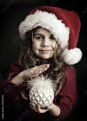 dziewczynka w czapce świętego mikołaja z bombką Poster