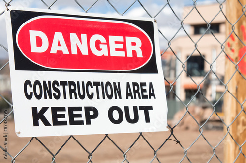 Poster Danger Construction area sign hanging on a chain link fence at a construction si