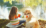 Two friends, child with Labrador retriever dog sitting in sunny - Fine Art prints