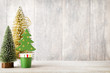 Artificial Christmas tree on a wooden background.