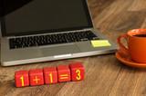 1+1=3 written on a wooden cube in a office desk