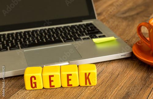 Poster Geek written on a wooden cube in a office desk