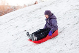 Child playing with sled in winter snow