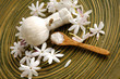 White flower with ball, salt in spoon in wooden bowl