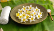 Many white flower with soap, salt in spoon in wooden bowl ,towel on banana leaf