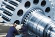 two mechanics with giant cogwheels and gears axles, steel industrial.