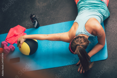 obraz lub plakat Woman worming up and stretching her body at the gym.Pilates.