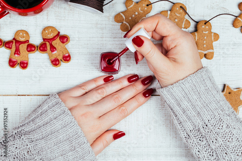 Holiday manicure treatment on a white wooden table decorated with homemade gingerbread cookies. Processed to retro film look.  © tamara83