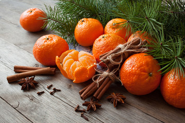 Tangerines on a wooden table with branches of fir