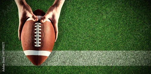 Fotobehang Voetbal Composite image of american football player holding up football