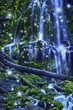 Waterfall with fairies and magical blue moonlight affect/Magical waterfall with fairies and blue misty water cascading over green mossy rocks