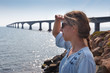 Woman looking at sea with Confederation Bridge in the background, Prince Edward Island, Canada