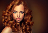 Fototapety Girl model with long red wavy hair. Big curls on the red head . Hairstyle  permanent waving