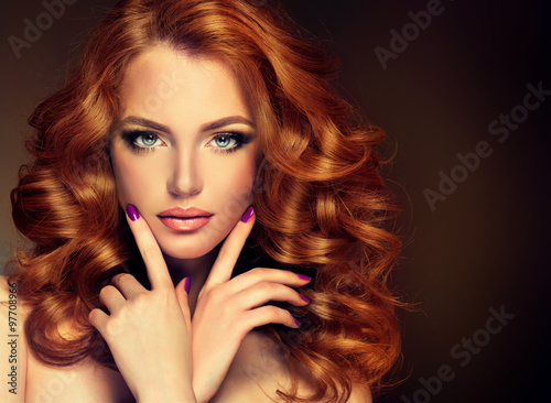 Fototapeta Girl model with long red wavy hair. Big curls on the red head . Hairstyle permanent waving
