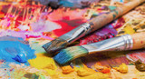 Fototapety Used brushes on an artist's palette of colorful oil paint