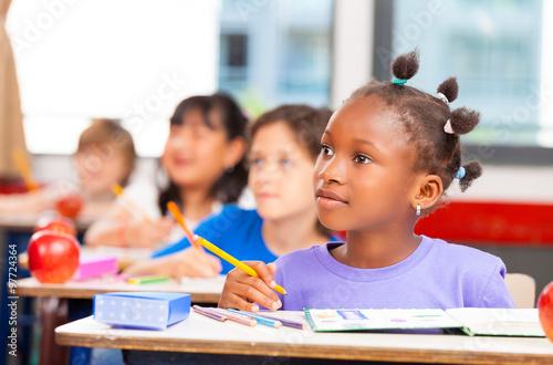 Fotografiet Happy children in a multi ethnic elementary classroom
