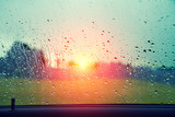 Driving a car in the rain. Sunset over field after rain through the wet window