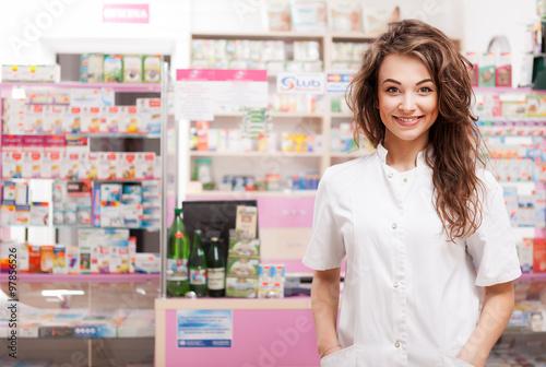 Aluminium Apotheek Smiling doctor in front of pharmacy desk
